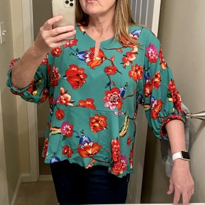 Person taking selfie photo in a mirror, wearing a floral top with a green background
