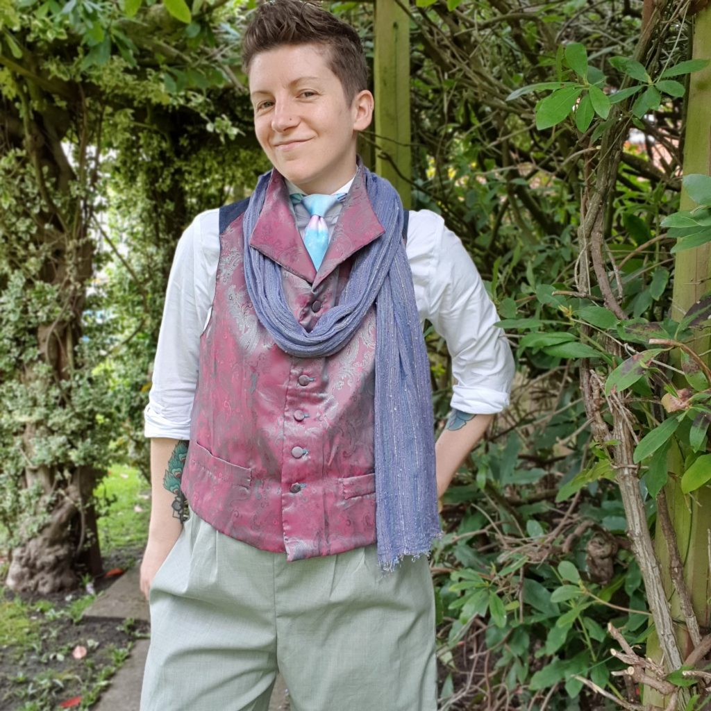 Photo of a person wearing a white shirt, dark pink waistcoat, blue tie and purple scarf with light green pants.  Trees are in the background.