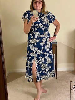 Photo of woman taking a mirror selfie wearing a blue dress with white flowers.